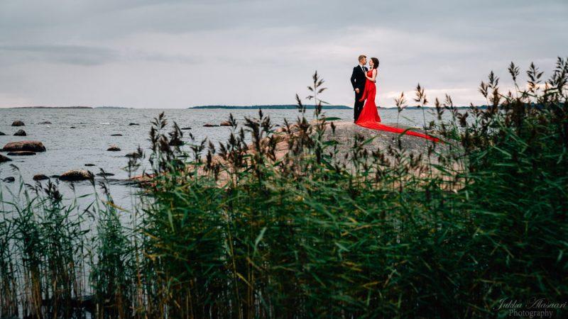 hääkuvaus hääpari rantakalliolla punainen mekko